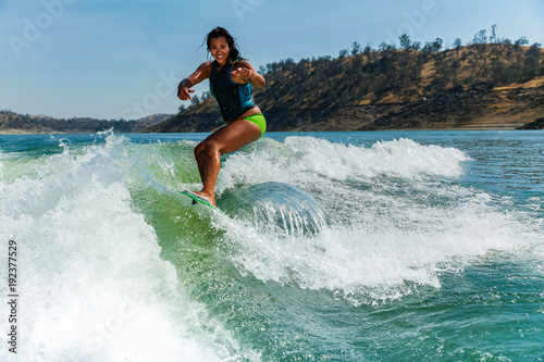 Fotografie, Obraz  Mixed race fit young woman wakesurfing on a lake in California on a clear summer