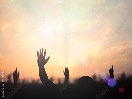 Valokuva  Resurrection of Easter Sunday concept: Silhouette christian people hand rising over blurred cross on spiritual light background