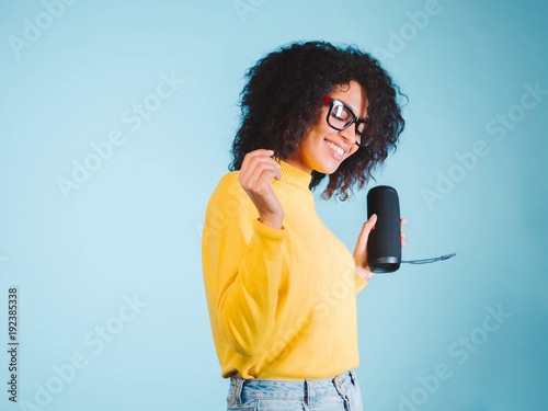Young beautiful african woman enjoying and dancing at blue background Canvas Print