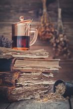 Cup Of Healthy Tea Or Herbal Tincture On Stack Of Old Books, Mortar Of Daisy Herbs. Hanging Bunches Of Medicinal Herbs On Background.