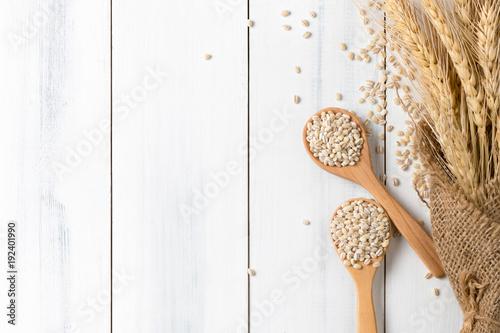 Fotografia Heap of pearl barley on wood spoon with ear of barley
