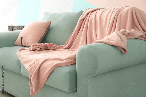 Obraz Comfortable mint couch with cushion and blanket in living room - fototapety do salonu
