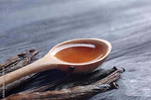 Foto auf Gartenposter Gewürze 2 Spoon with vanilla extract and sticks on wooden background
