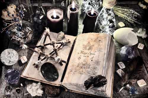 Open witch book with pentagram, black candles, stones, crystals and magic ritual objects. Halloween, occult, esoteric and wicca concept. Vintage background