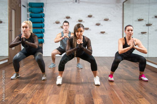 Fotografie, Obraz  Young sporty people exercising together in sumo squat pose at gym