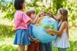 Leinwanddruck Bild - Kinder halten zusammen eine Weltkugel