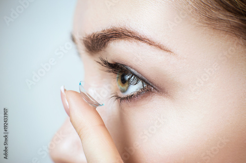 Fotografía  Close-up shot of young woman wearing contact lens.