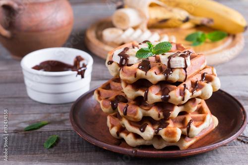 Fotografía  Homemade Belgian waffles with chocolate sauce and banana slice on a plate