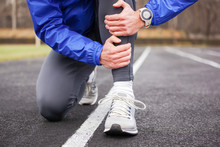 Cropped Shot Of A Young Runner Holding His Leg In Pain.