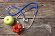 Stethoscope strawberry and green apple on wood