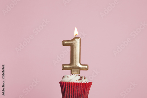 Photo  Number 1 gold candle in a cupcake against a pastel pink background