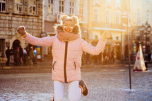 Outdoor Portrait Of Playful Fashionable Blond Woman In Sunglasses Wearing Stylish Pink Winter Puffer Coat, Gloves And Scarf Jumping On City Street. Girl Enjoying Winter Day In Street Of European City.