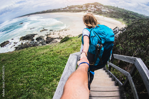 Couple summer vacation travel. Woman walking on romantic honeymoon promenade holidays holding hand of husband following her, view from behind