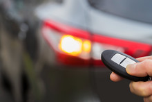 Close Up Of Driver Activating Car Security System With Key Fob