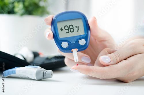 Fotografía Woman checking blood sugar level by glucometer