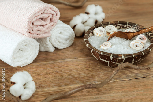 Foto op Plexiglas Spa Spa set with sea salt in bowl and rolled soft clean towels on brown wooden background. Copy space. Spa concept natural rustic.