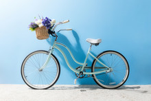 Side View Of Bicycle With Flowers In Basket In Front Of Blue Wall