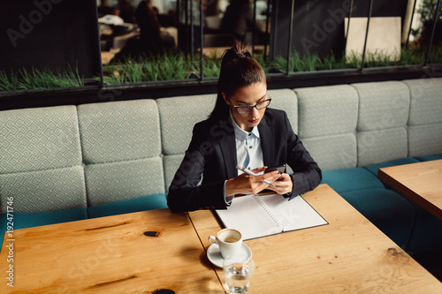 Poster  Portrait of young businesswoman in cafeteria.