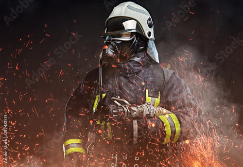A firefighter dressed in a uniform in a studio. Tableau sur Toile