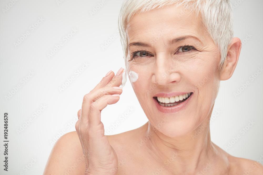 Fototapeta Head shot of beautiful senior woman putting on the creme.