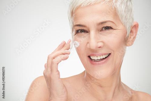 Fotografía  Head shot of beautiful senior woman putting on the creme.