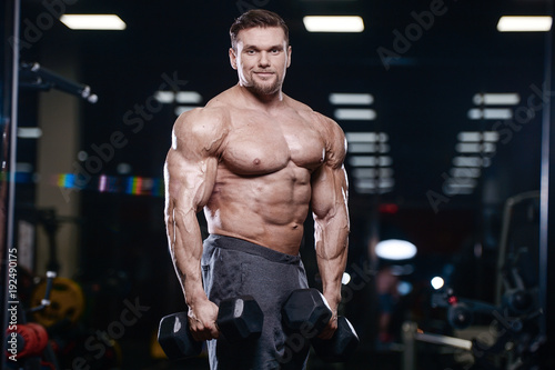 Cuadros en Lienzo Brutal strong bodybuilder athletic men pumping up muscles with dumbbells