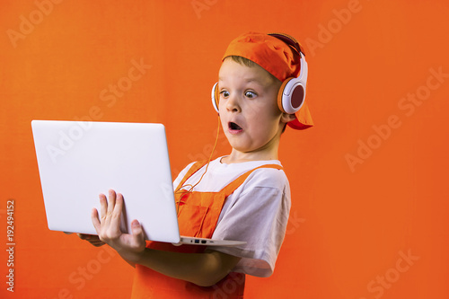 Fotografia  funny boy builder in headphones and laptop doing repairs on bright background