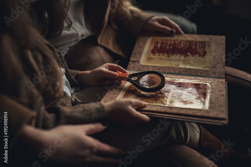 Fotografía  Child girl with woman in image of Sherlock Holmes sits and looks photoalbum with magnifier