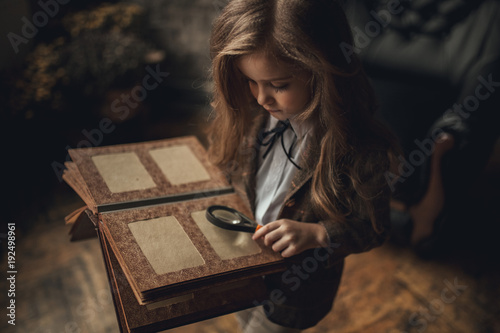 Fotografia  Child girl in image of Sherlock Holmes stands in room and looks photoalbum with magnifier on background of old interior