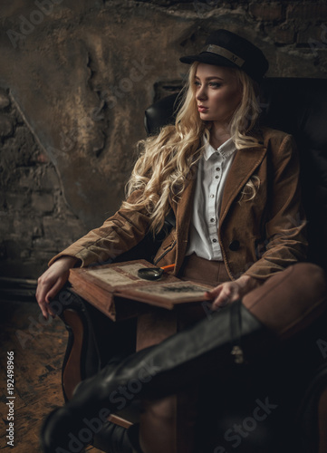 Платно Young pensive woman in image of Sherlock Holmes sits in armchair and holds photoalbum in her hands with magnifier on background of old interior