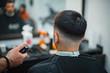 Man gets a cool haircut in barbershop. Barber makes the cut man electric razor. Men's care head. Soft focus.