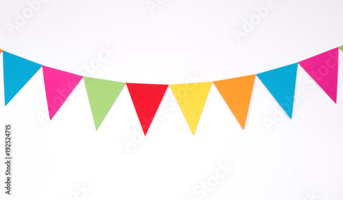 Fotografia  Colorful hanging paper flags on white wall background, decor items for party, fe