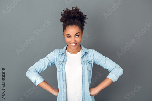 Young african woman isolated on grey wall studio casual daily lifestyle hands on waist