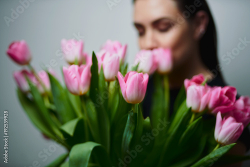 Láminas  Portrait of attractive young woman with tulips is standing in light room and smiling
