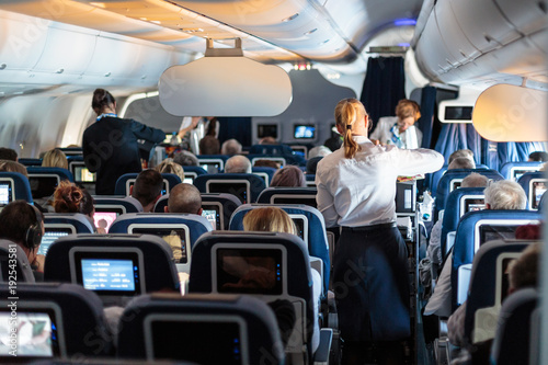 Interior of large commercial airplane with flight attandants serving passengers on seats during flight. Stewardesses in dark blue uniform walking the aisle. Horizontal composition.