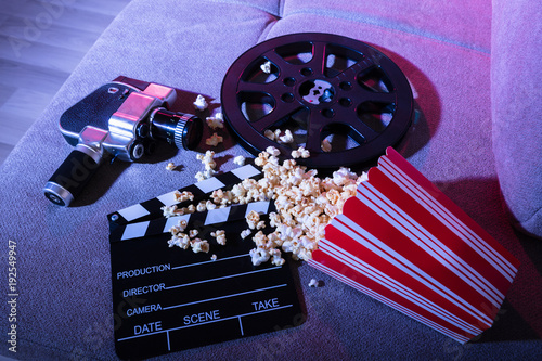 Fotografering  Spilled Popcorn With Clapperboard And Movie Camera