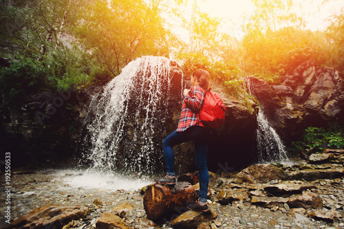 Fotografija  Young woman backpacker looking waterfall in forest