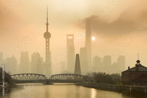 Foto op Plexiglas Shanghai Shanghai Financial Center and modern skyscraper city in misty gold lighting sunrise behind pollution haze, view from the bund in Shanghai, China. vintage picture style