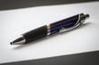 Office ballpoint pen lies on a sheet of paper close-up.