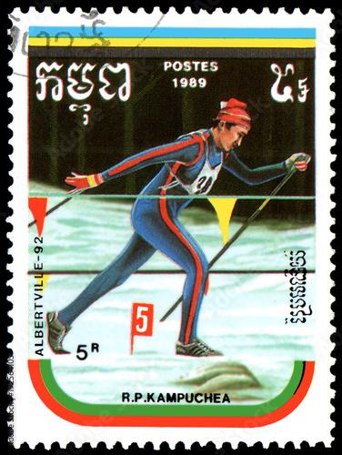 Fotografia  REPUBLIC OF KAMPUCHEA (CAMBODIA) - CIRCA 1989: postage stamp, printed in Republic of Kampuchea, shows a cross-country skiing