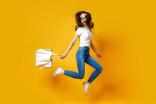 Beautiful Young Woman In Sunglasses, White Shirt, Blue Jeans Posing, Jumping With Bag On The Yellow Background