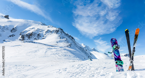 Photo of crossed skis and sticks against background of snowy landscape