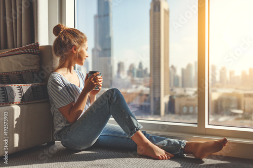 happy young woman drinks coffee in morning at window