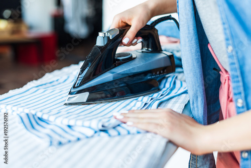 Fotografie, Obraz close-up partial view of young woman ironing clothes at home