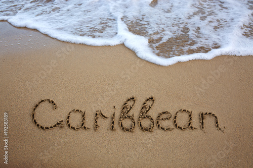 Foto op Plexiglas Caraïben Word Caribbean written on the sand near the sea.