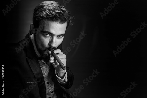 Obraz na plátně  bearded, business man in suit, smokes a cigar and looks into the camera, image w