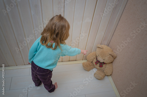 Fényképezés  girl, child punishes, puts in the corner of the toy bear