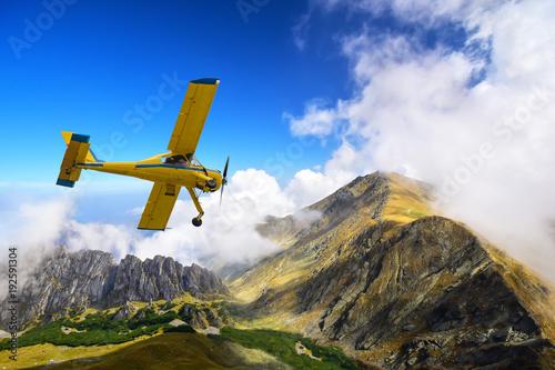 Naklejka premium Stary i zabytkowy samolot cessna latające nad karpackimi szczytami górskimi w Rumunii
