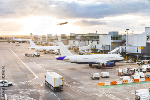 Fotografie, Obraz  Busy airport view with airplanes and service vehicles at sunset