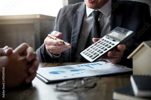 Fototapeta Real estate broker agent being analysis and making the decision a home estate loan to customer, Agent man is using calculator to presentation detail and waiting for his reply to finish obraz